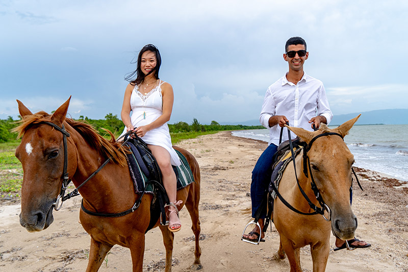 couple riding horses on negril beach