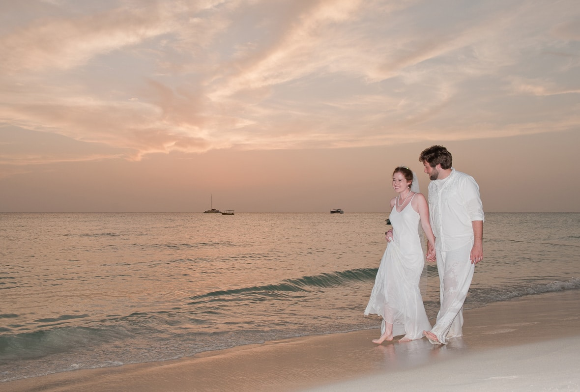 Married couple walking along the beach