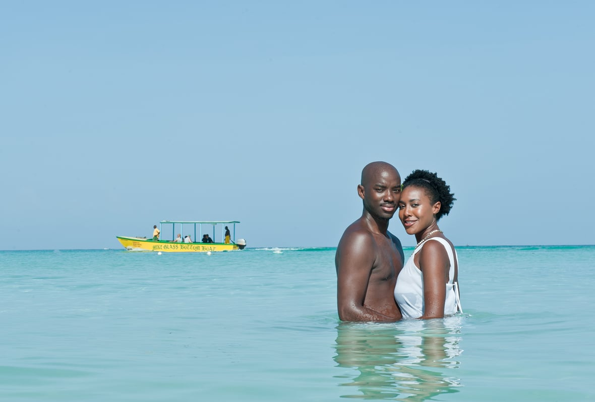 married couple in the water with boat