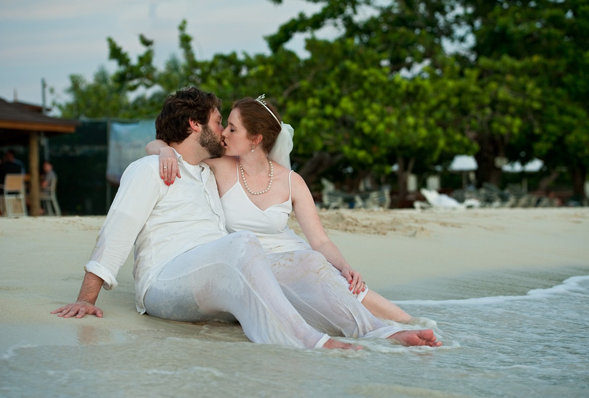 married couple sitting on the beach